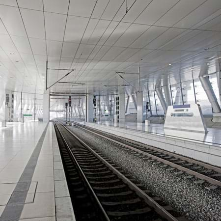 A photo shows the interior tunnel of a modern railway station with two sets of train tracks, ceiling, windows and waiting platforms.