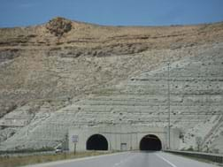 Photo shows view from a highway looking at two arched tunnel entrances into the rock face of a mountain.