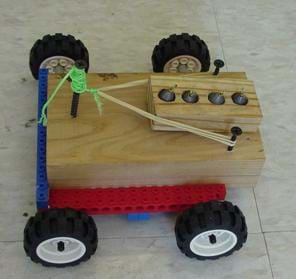 A photograph shows a block of wood placed on a LEGO-type platform onto which four small rubber wheels are attached. A second, smaller wooden block with weights (fishing sinkers) resting inside four holes in the block rests on the bigger wooden block, and will be launched off the back of the vehicle via a rubber band.