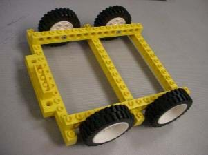 A photograph shows a LEGO chassis with four wheels on which the wooden block will be placed so that the vehicle can roll.