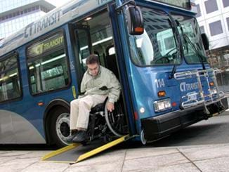 A photograph of man in a wheelchair who is exiting a public city bus via a ramp. One end of the ramp is placed on the bus steps, while the opposite end is placed on the sidewalk.