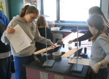 A photograph of students at lab table preparing to measure their cars pulling weight up an inclined plane. Shown are two wood planes attached with a clamp to a stand.