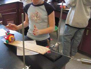 A photograph of a student at lab table watching a toy airplane being pulled up inclined plane.