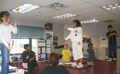 A photograph of many students standing on their desks in a classroom. The girls and boys are attaching their pulleys to the ceiling.