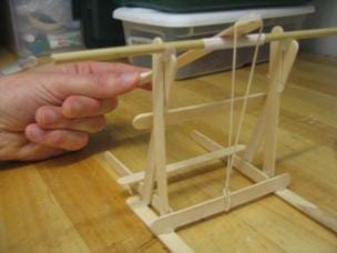 A photograph of a finished catapult constructed by students with tongue depressors and popsicle sticks.