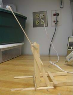 A photograph of a finished catapult. Front and rear stabilizers keep catapult from flipping. A straw is added to the end of the tongue depressor to prevent the grapes from sliding off during launch.