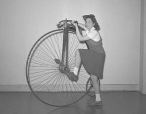 A black and white photograph of a girl getting on an old bicycle. The bicycle has one big front wheel and a small back wheel.
