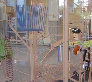 Photo shows a Rube Goldberg machine, a complex system of loops and tracks to simply move a ball throughout a large plastic-enclosed box.