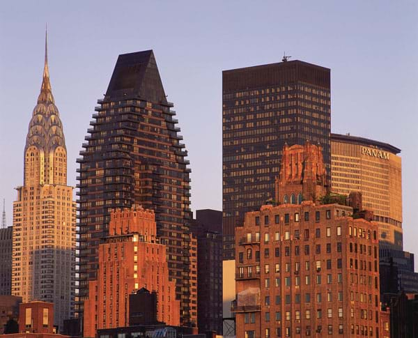 Photograph of pyramid-shaped tops of skyscrapers in orange light of sunset.