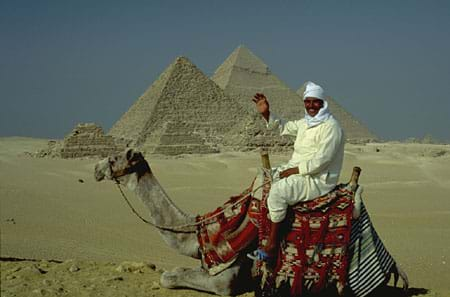 Photograph of a man on a camel in front of five pyramids in a desert.