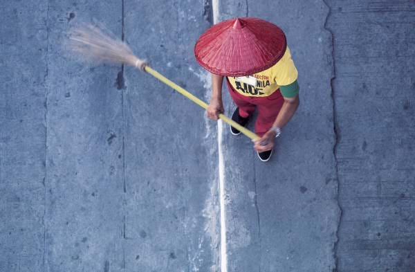 Photograph from above, showing a person sweeping with a broom.