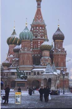 Photo of red brick towers with colorful onion-shaped domes.