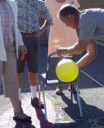 Photo shows a person positioning an inflated balloon to be released along a taught string attached to the back of a chair.