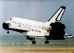 Photo shows a US space shuttle landing, with its rear wheels about to touch the runway and its nose and front wheels still in the air.