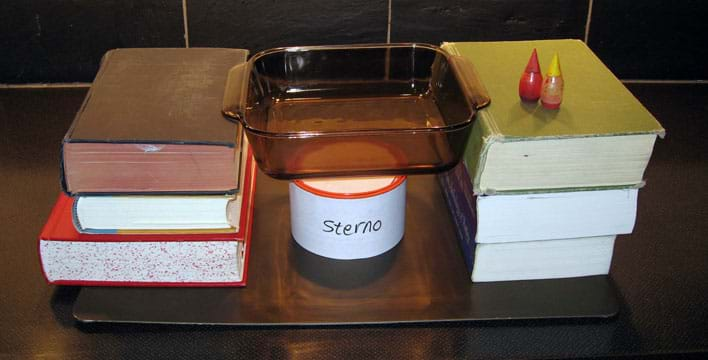 A glass baking dish is suspended by stacks of three books on each side over a can of sterno. Food coloring bottles are nearby.