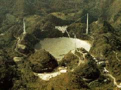 Photo shows a huge dish inset into a forested valley, with structures and towers around it.