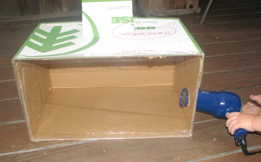 Photo shows a closed cardboard box with one side replaced with clear Plexiglas, and hairdryer nozzle inserted into round hole on one side.