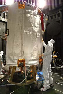 A man in a white jumpsuit examines the white material covering a structure about 3m high x 2m wide in size.