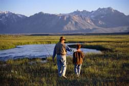 Photo shows a man and boy fishing in a field by a pond with mountain and sky in the background.