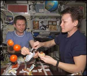 Photo shows a man and a woman holding food and using utensils as three oranges float nearby.
