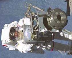 Photo shows a person in a white space suit floating by some equipment, with the surface of the Earth as the background.