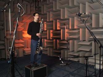 Photo shows a man playing a saxophone surrounded by microphones in a room with walls covered in acoustical tiles.