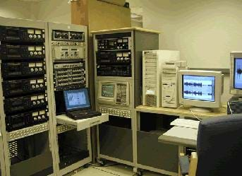 Photo shows a room full of equipment, computers and monitors.