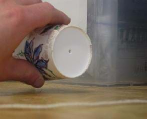 Photo shows a hand holding a paper cup tipped sideways showing a hole in its bottom.
