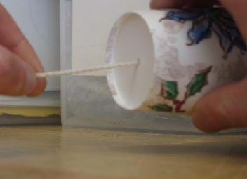 Photo shows one hand holding a paper cup sideways with a string coming out of the bottom and fingers of another hand pulling the string tail taut and away from the cup.