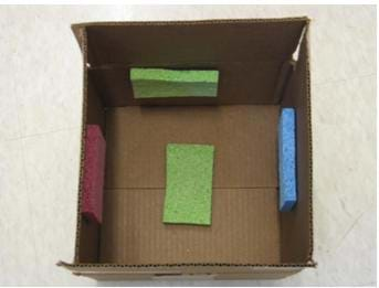 Photo looking into a box from above with sponges attached to the bottom and inside four walls.