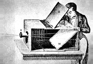 A pen and ink drawing shows a man drawing an image as it appears in a mirror on the top of the camera obscura. The camera is a large box on a table. Light (thus, an image) enters through a hole, is reflected off a mirror and the image is reflected onto another mirror on the top of the box.