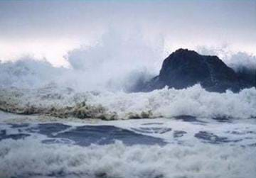 Image of waves crashing against a lone rock in the ocean.