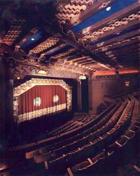 A photograph of the KiMo Theatre in Albuquerque, NM. Shown are rows of curved seats, each row rising above the previous row, a stage with a red curtain and corrugated panels on the ceiling.