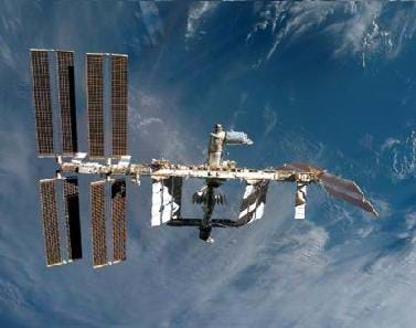 Photo shows the Earth's blue, cloudy atmosphere behind a leggy, floating structure with solar panels.