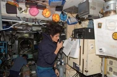 Photo shows a female astronaut talking on a handheld device while floating in a scientific laboratory. Another astronaut in the background is collecting data on a computer.