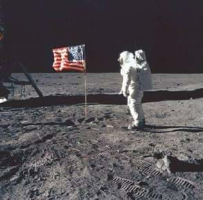 Photo shows a man in a space suit on the moon surface next to an American flag.