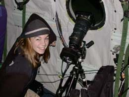 A young girl smiles as she stands near what appears to be a long-lens camera on a tripod that is directed out a porthole window.