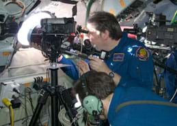 Photo shows two men in blue jump suits operating what looks like a large camera on a tripod facing out a porthole window.