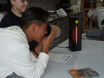 A student looks through a finished spectrograph at a gas discharge tube.