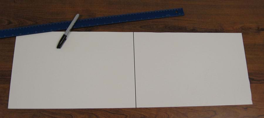 Photo shows a black line equally splitting a rectangular piece of white paper.