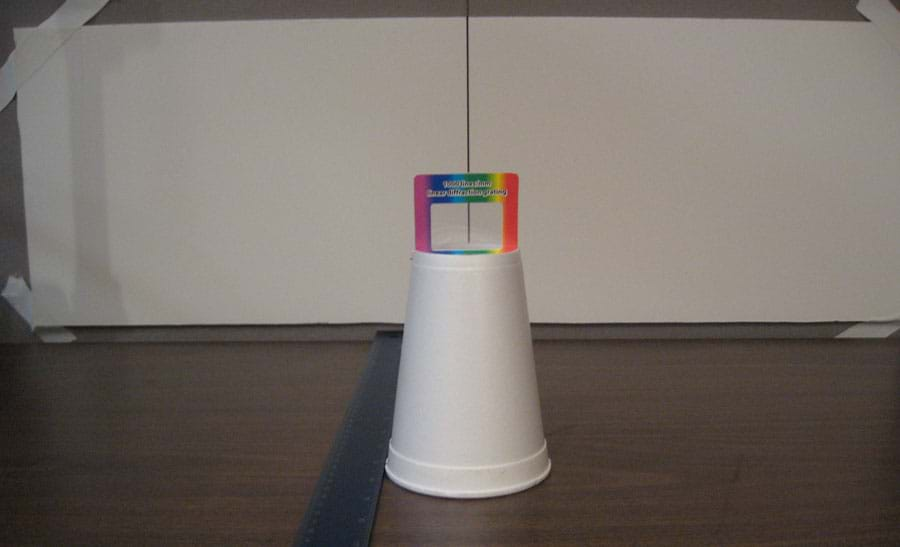 Photo shows an upside-down cup on a tabletop, lined up in front of a black vertical line in the middle of a wide white paper taped to the wall behind, with a ruler positioned on the table nearby.
