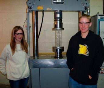 A photograph shows two students standing in front of a compression testing device with an acrylic plastic tower ready to be compressed.