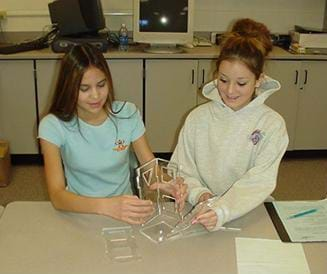 A photo shows two female teens building their acrylic tower.