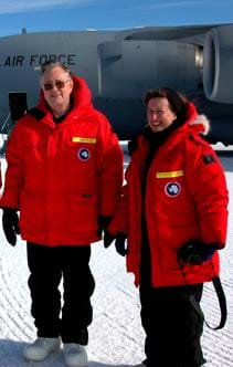 Photo shows two adults wearing bright red parkas as they stand near an Air Force jet parked on snow-packed ground.