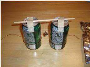 Photo shows two soda cans, placed two inches apart, and connected by a wooden dowel with a bell hanging by a thread from the middle of the dowel.