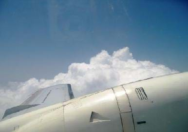 Photo from the window of an airplane shows airplane wing, blue sky and a patch of clouds.