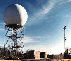 Photo shows Doppler radar equipment, which looks like a giant white ball resting atop a three-story metal stair structure.