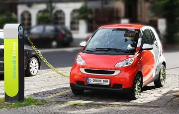 An electric car recharging its battery at a Renewable Energy charging post.