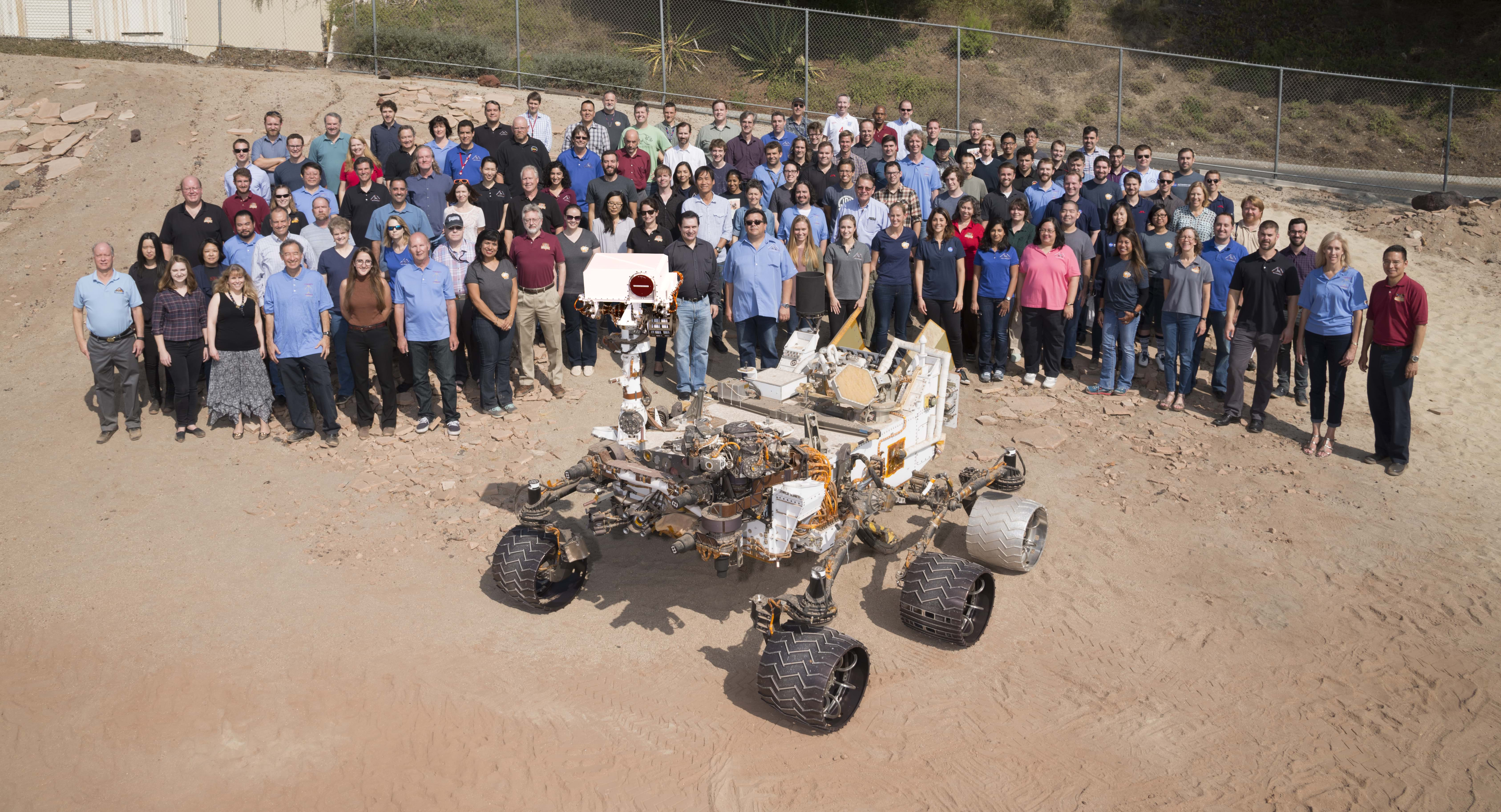 Mars rover model of Curiosity with its team