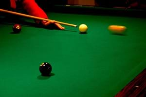 A pool table showing a white cue ball about to hit a pool ball.